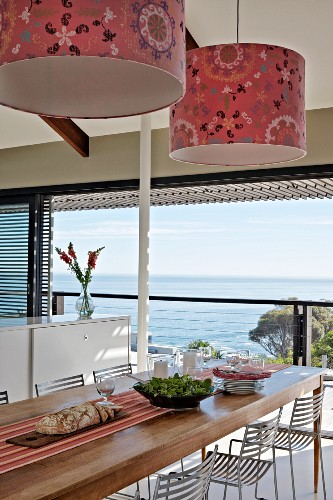 Pendant lamps with patterned, fabric lampshades above dining table and metal chairs next to panoramic window with sea view