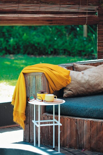 Wooden bench with seat cushions and yellow blanket in front of rolled up bamboo blind