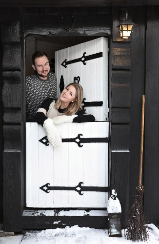 Young couple standing in white stable door of black wooden cabin