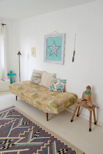 Buddha statue on stool next to 60s-style couch below picture of star on wall