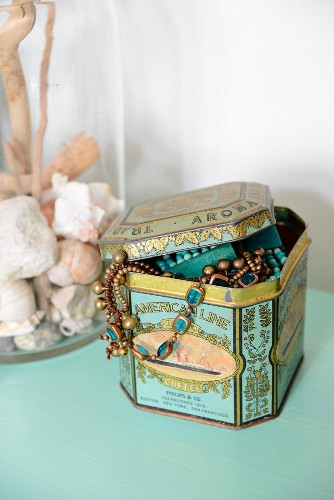Jewellery in tin and collection of seashells in glass container