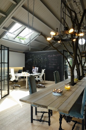 Dining table surrounding tree trunks, pendant lamp with wrought iron hoop and work stations in loft-style interior