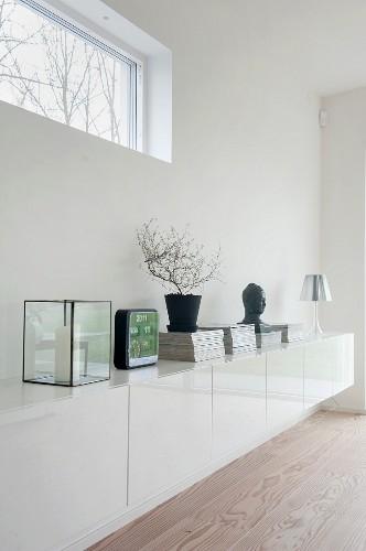 White sideboard against wall below ribbon window