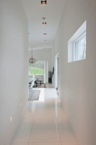 Narrow hallway with white tiled floor leading to living area