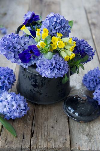 Hyacinths, cowslips and violas in enamel jug