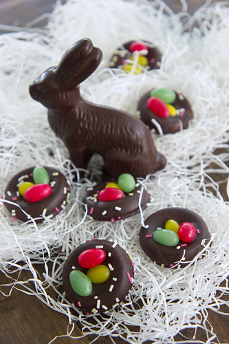 Chocolate Easter bunny amongst shredded paper and sugar nests