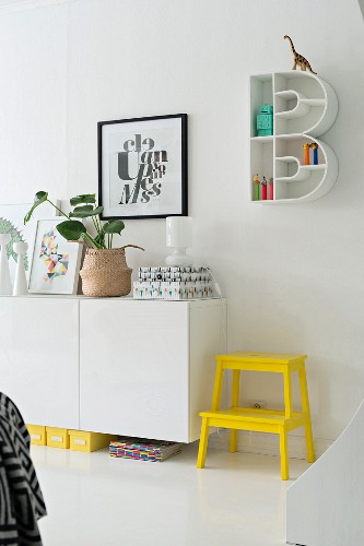 Bright yellow step stool next to sideboard below B-shaped shelving unit