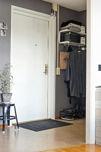 Hallway with grey-painted walls, white front door and minimalist cloakroom area