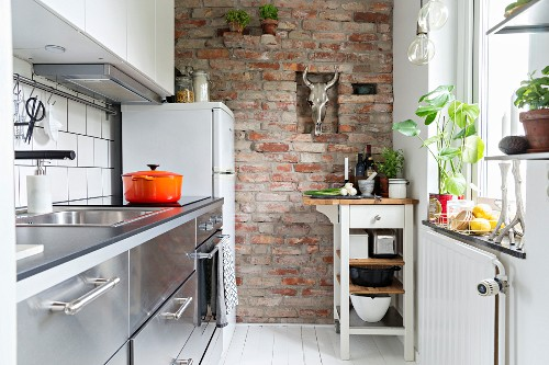 Brick wall and serving trolley in narrow kitchen