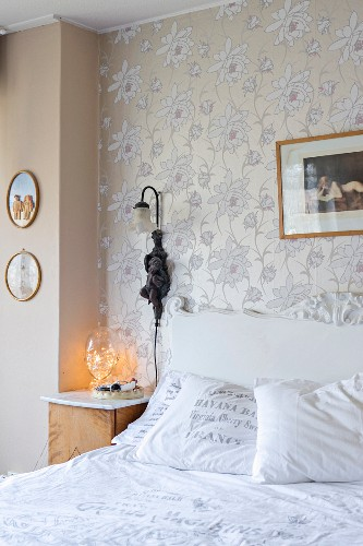 Vintage-style double bed with carved headboard below antique sconce lamp on floral wallpaper