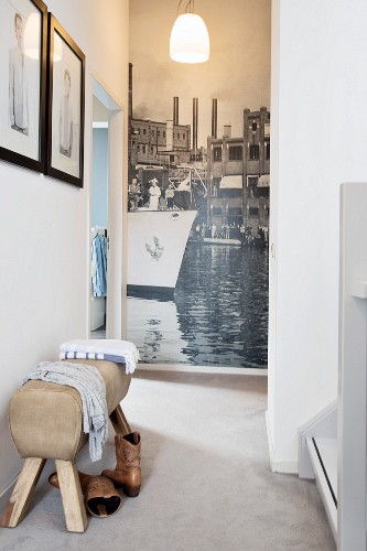 Vaulting-horse-style bench in hallway with photo mural at far end
