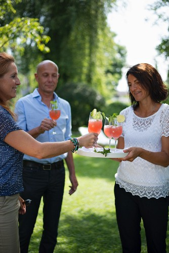 Three friends enjoying cocktails in garden