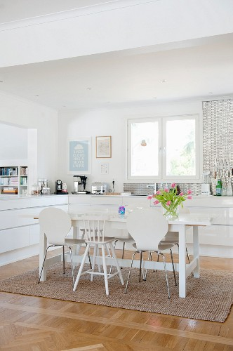 Various white chairs around dining table in open-plan modern fitted kitchen