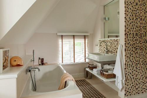 Modern attic bathroom: Bathtub with wall-mounted taps opposite washstand and pale brown mosaic wall tiles