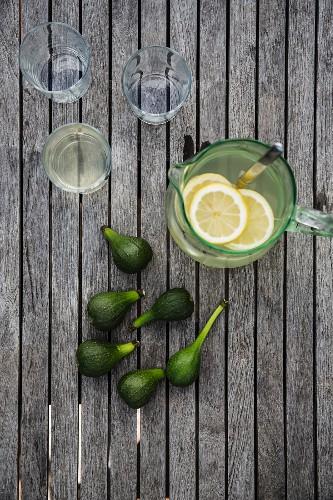 Slices of lemon in glass vase of lemonade, drinking glasses and fresh green figs on wooden surface