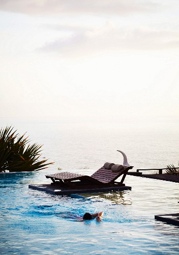 Comfortable wooden lounger next to infinity pool with sea view