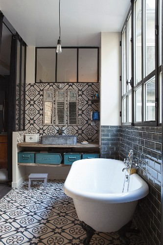 Ornate tiles, free-standing bathtub, industrial window and rustic washstand with metal containers on shelf in bathroom