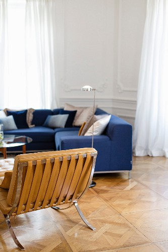 Blue sofa and leather armchair in period apartment