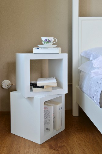 Books and teacup on two stacked cube-shaped shelves next to white bed with lace-trimmed bed linen