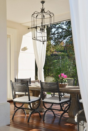Stone table and wrought iron chandelier in elegant loggia seating area with garden view