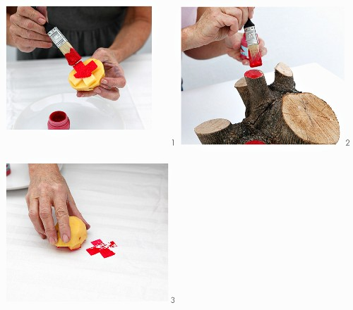 Painting both a potato stamp with cross motif and the cut surfaces of a wooden stump red