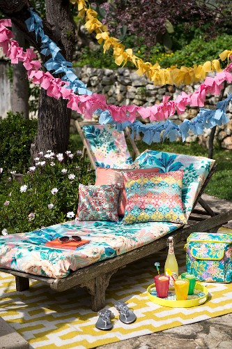 Lounger and cushions below garlands in colourful seating area in garden