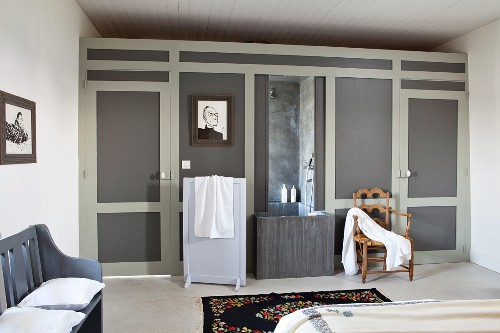 Shower area integrated into elegant partition wall in bedroom