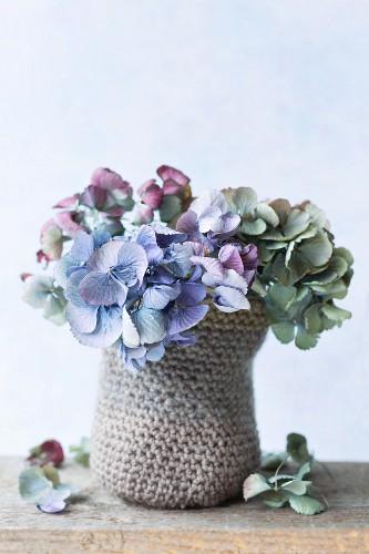 Posy of dried hydrangea flowers in small crocheted basket