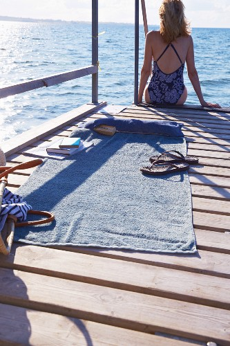 Woman sitting on jetty next to beach towel and denim bag