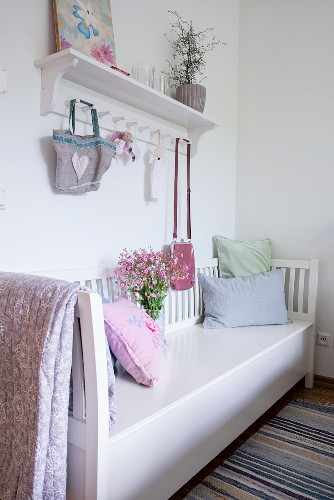 White-painted bench below wall-mounted shelf with bags hanging from hooks