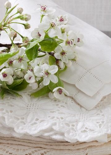 Branches of apple blossom on stacked doilies