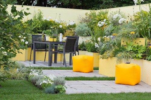 Terraced flowerbeds in various shades of yellow in courtyard garden