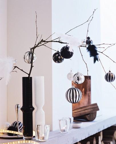 Elegant baubles and bird ornaments on bare branch in black vase