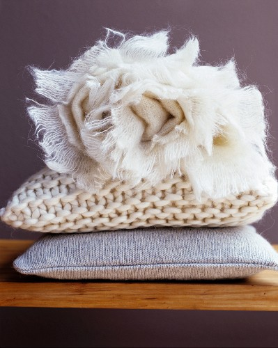 Cosy cushions and rolled, off-white blanket