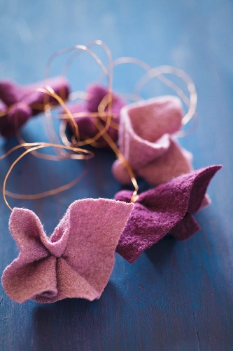 Pieces of felt in berry shades tied with copper wire