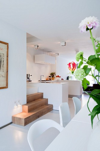 View past flowers on table into modern, open-plan kitchen