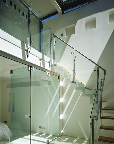 Open stairway with sliding glass doors and steps with glass banister