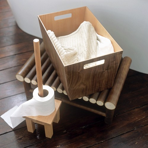 A toilet roll holder next to a basket of towels