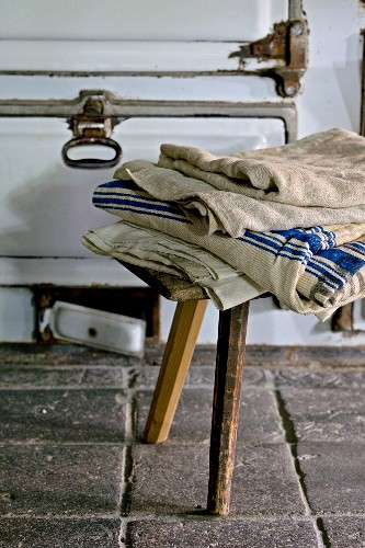 Folded cloths on rustic wooden stool on old tiled floor