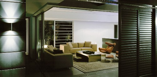 View into living room with sofas, coffee table & armchairs