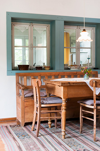 Pale wood dining table, chairs and bench below window in loggia with vintage pendant lamp