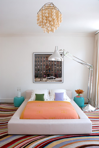 Bright bedroom with silver, oversized anglepoise lamp, double bed with white leather surround and colourful carpet with pattern of curved stripes