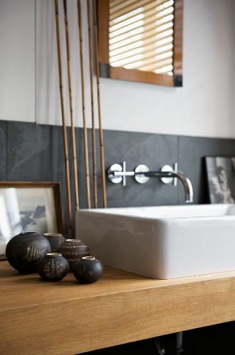 White countertop washbasin on wooden washstand decorated with small, anthracite-coloured ceramic vases