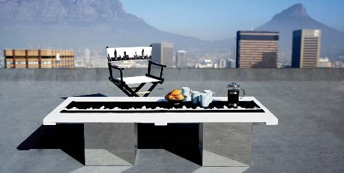 Handmade prints of New York skyline on breakfast table and directors' chair on roof terrace with magnificent view of Table Mountain