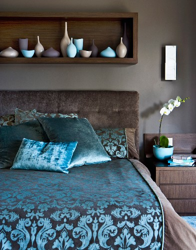 Elegant bed with patterned satin cover against brown-painted wall