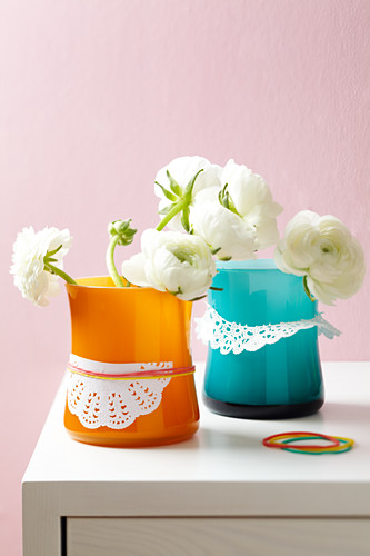 Buttercups in vases decorated with doilies