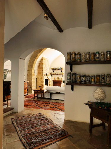 Collection of ceramic vases on shelves next to arched doorway with view into Mediterranean living room