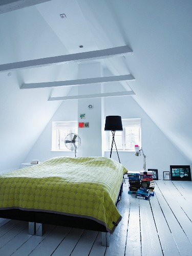 Bed with yellow bedspread on rustic floorboards in converted attic room