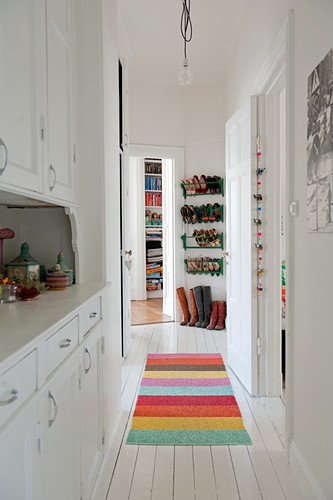 Narrow hallway with white fitted cupboard and multi-coloured rug on white wooden floor