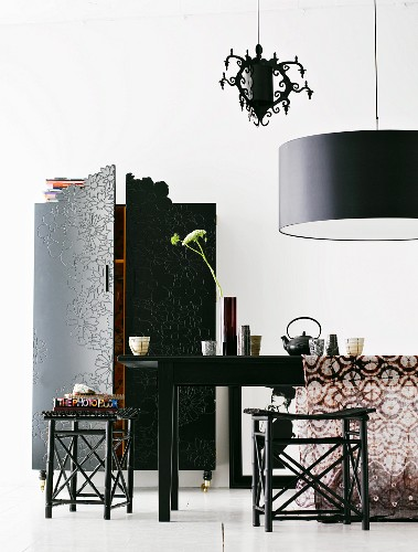 Oriental-style, dark wood stools at table below designer pendant lamp